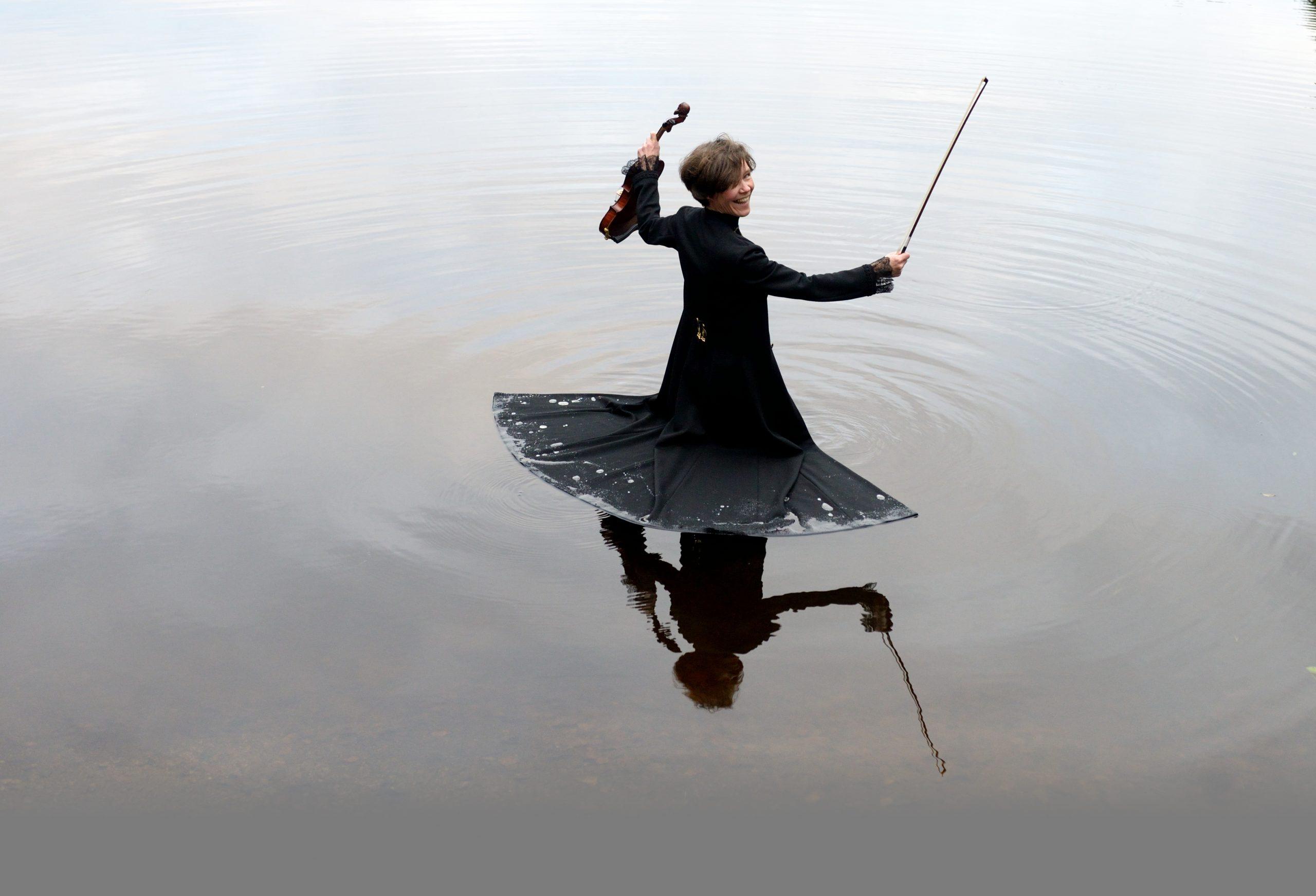 Kuvassa Johanna Almark seisoo vedessä kädessään viulu