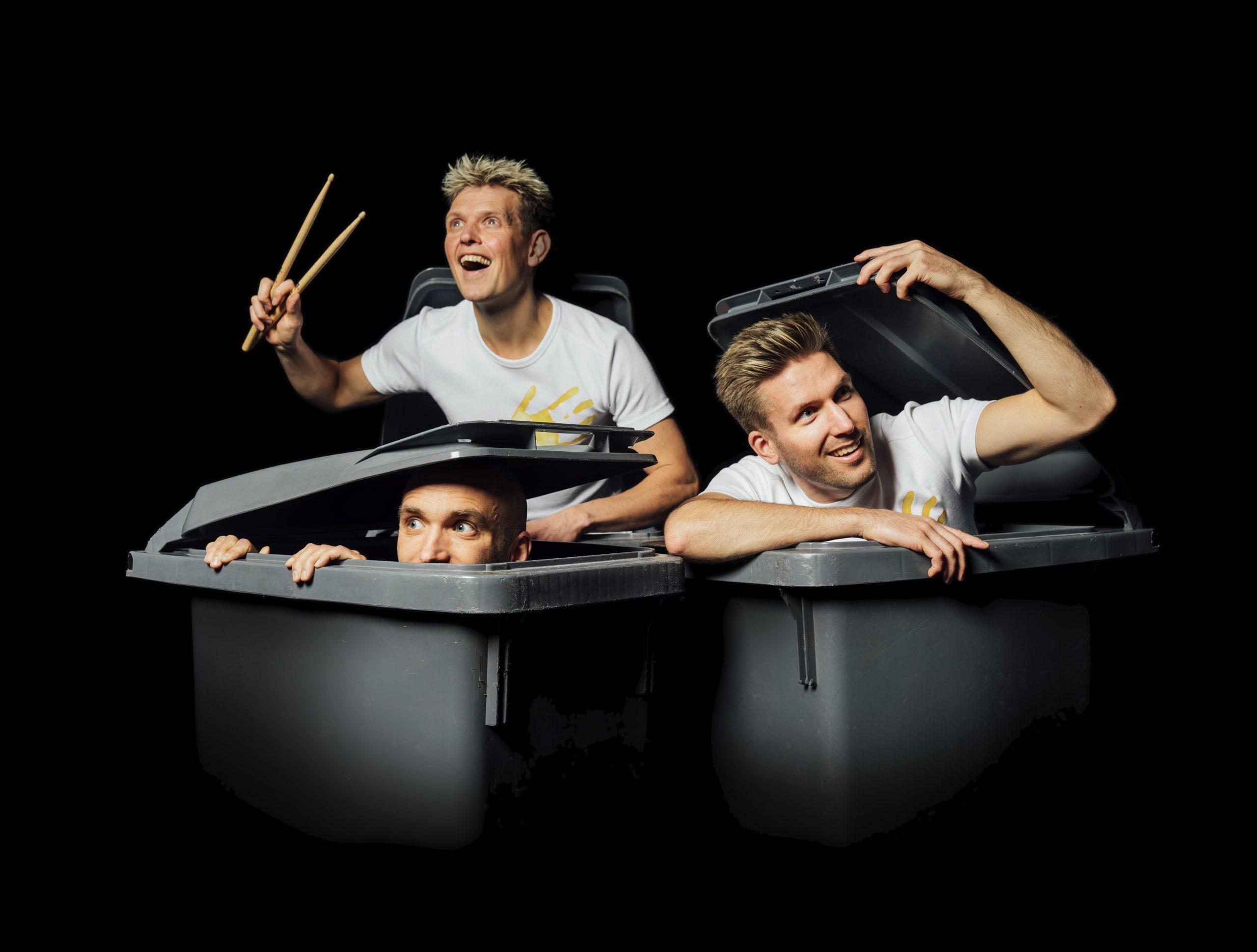 Kuvassa kaksi yhtyeen jäsentä kurkistaa roskalaatikosta ja kaikki jäsenet katsovat eri suuntiin.