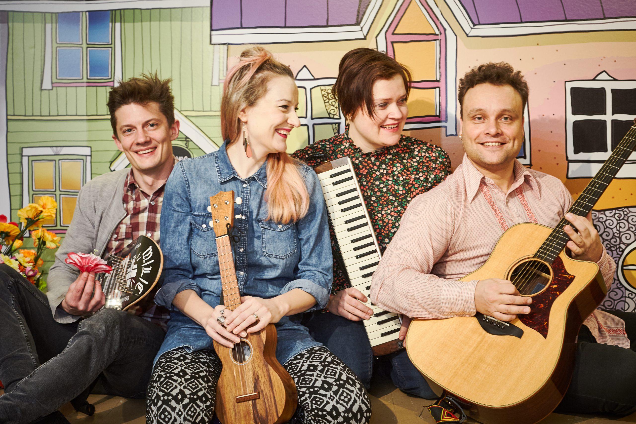 Kuvassa Juurikadun orkesterin jäsenet istuvat hymyillen soittimet kädessä talomaiseman edessä.