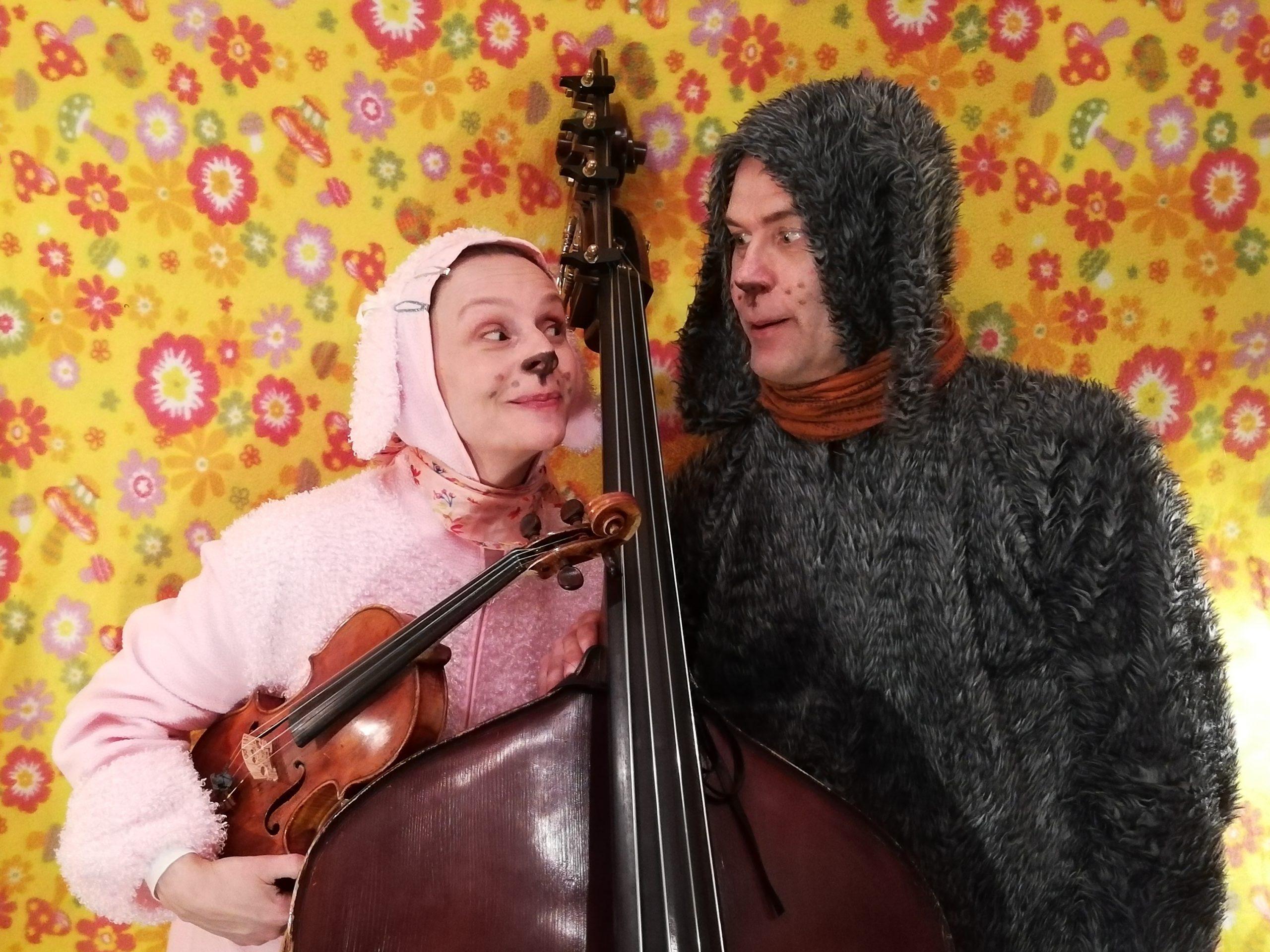 Klasari-Klaara ja Jazz-Piski soittimet kädessään värikkään taustan edessä virne kasvoillaan.