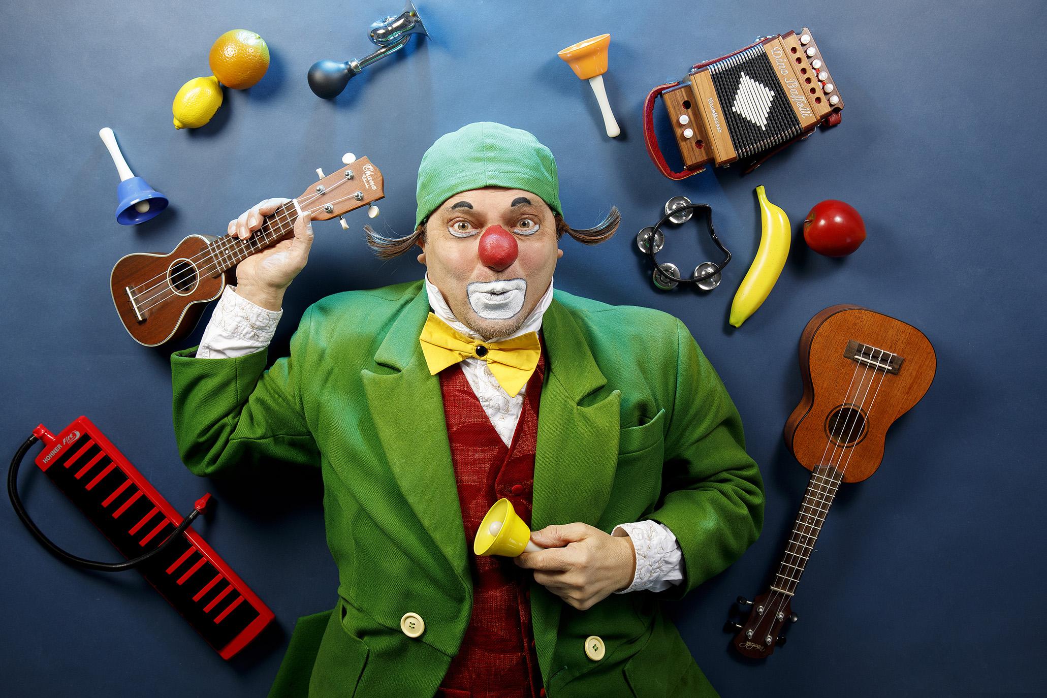 Klovni Dodo ympärillään ukulele, melodica, haitari, rytmisoittimia ja banaani