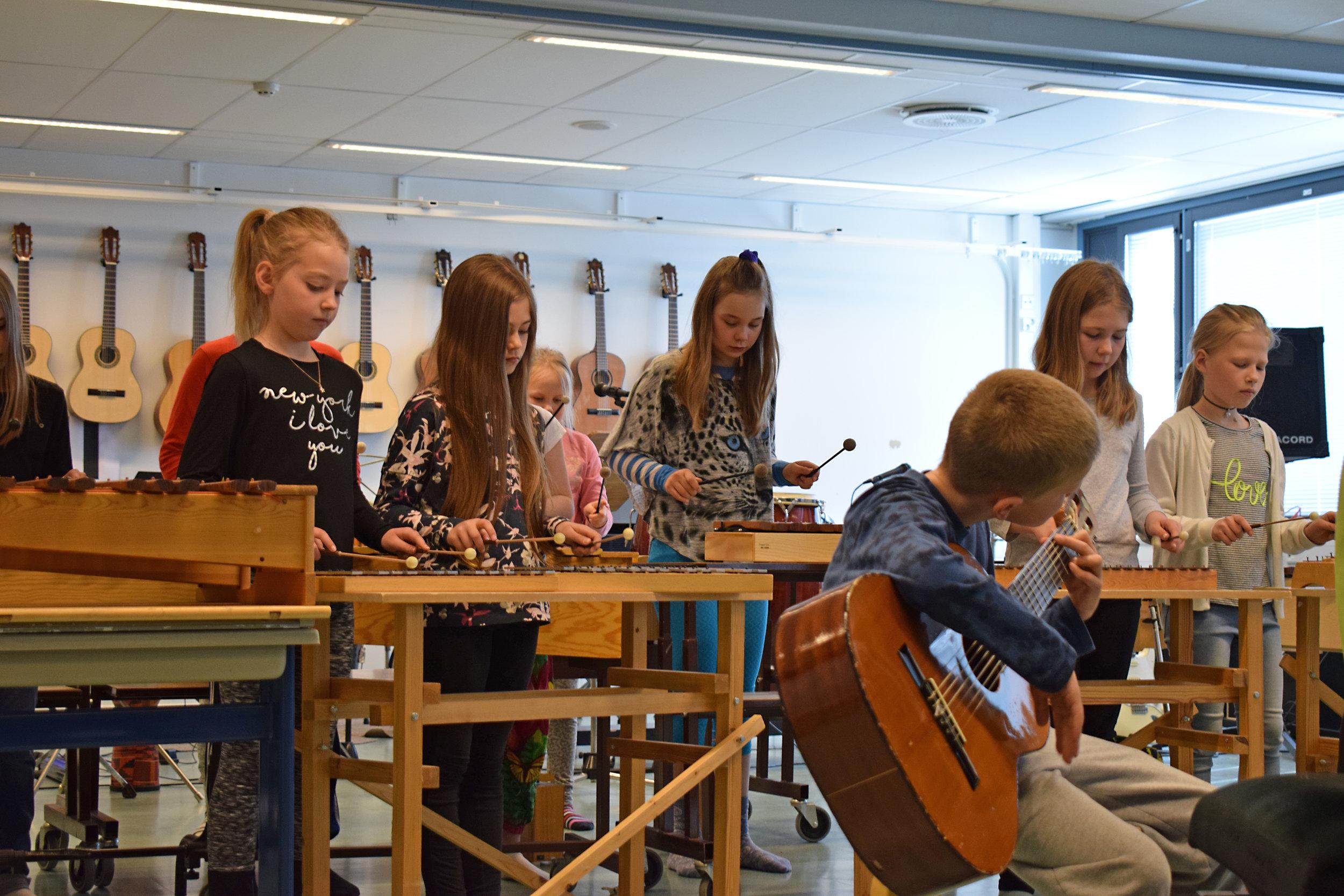 Oppilaita soittamassa erilaisia soittimia