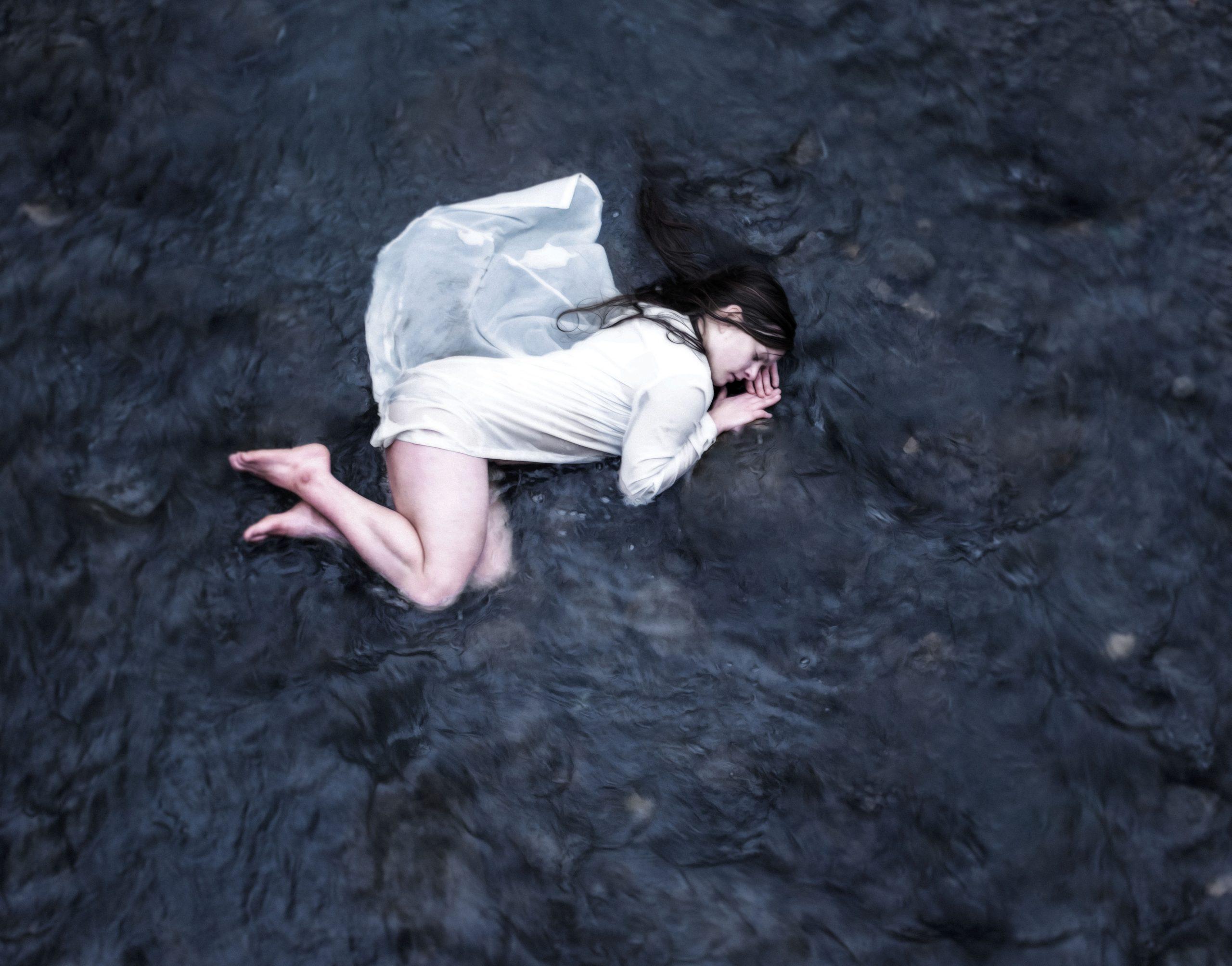 makaa vedessä valkoinen mekko päällään.