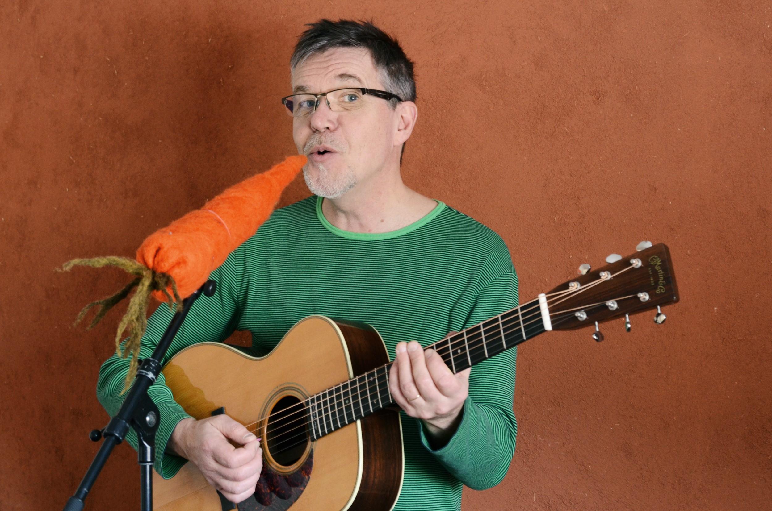 Pentti Rasinkangas laulaa kitaran kanssa mikrofonina iso pehmo porkkana.