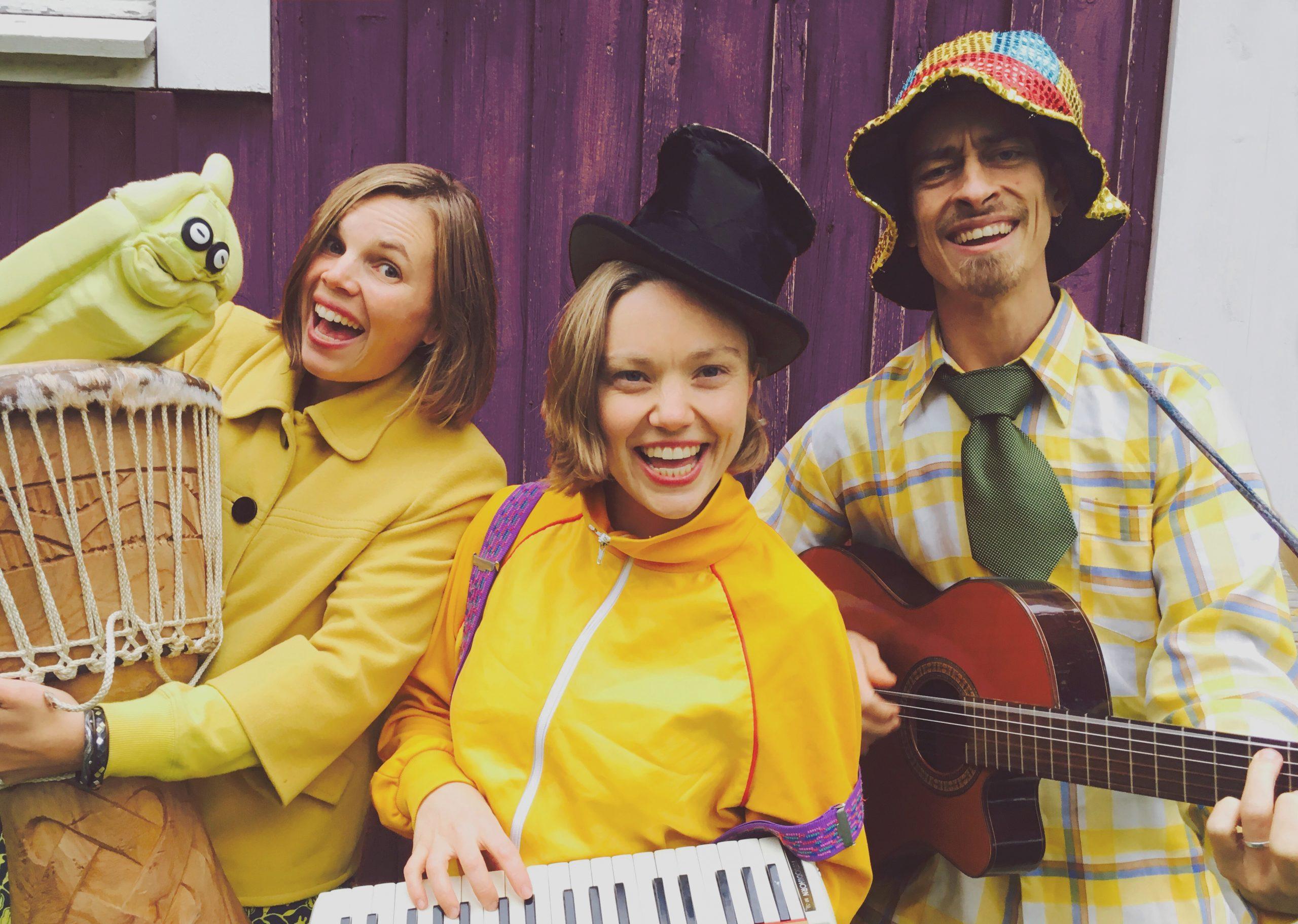 Kuvassa Raka Bananer yhtyeen laulaja lautaseinän edessä soittimet kädessään.
