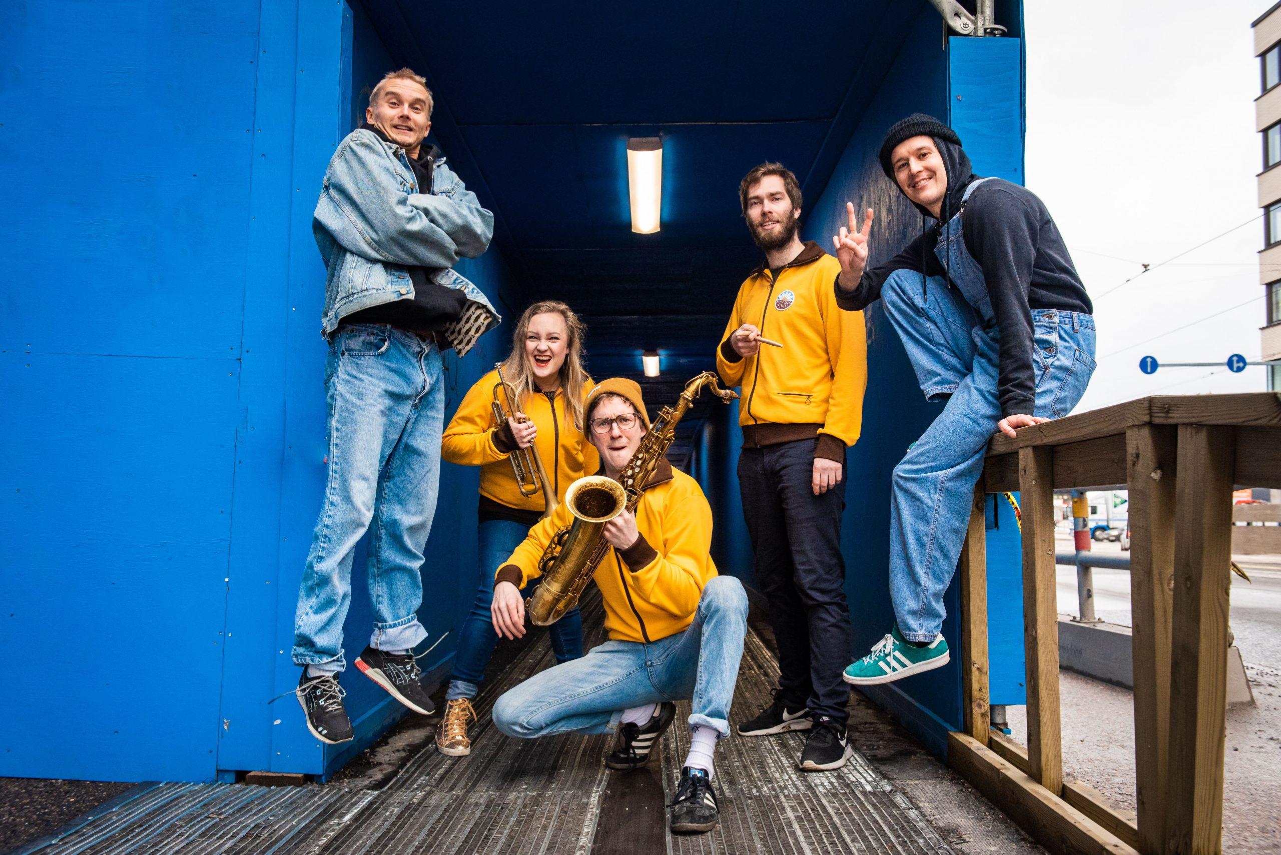 Kuvassa School Breaks yhtye ulkona teräskontin edessä soittimet kädessään.
