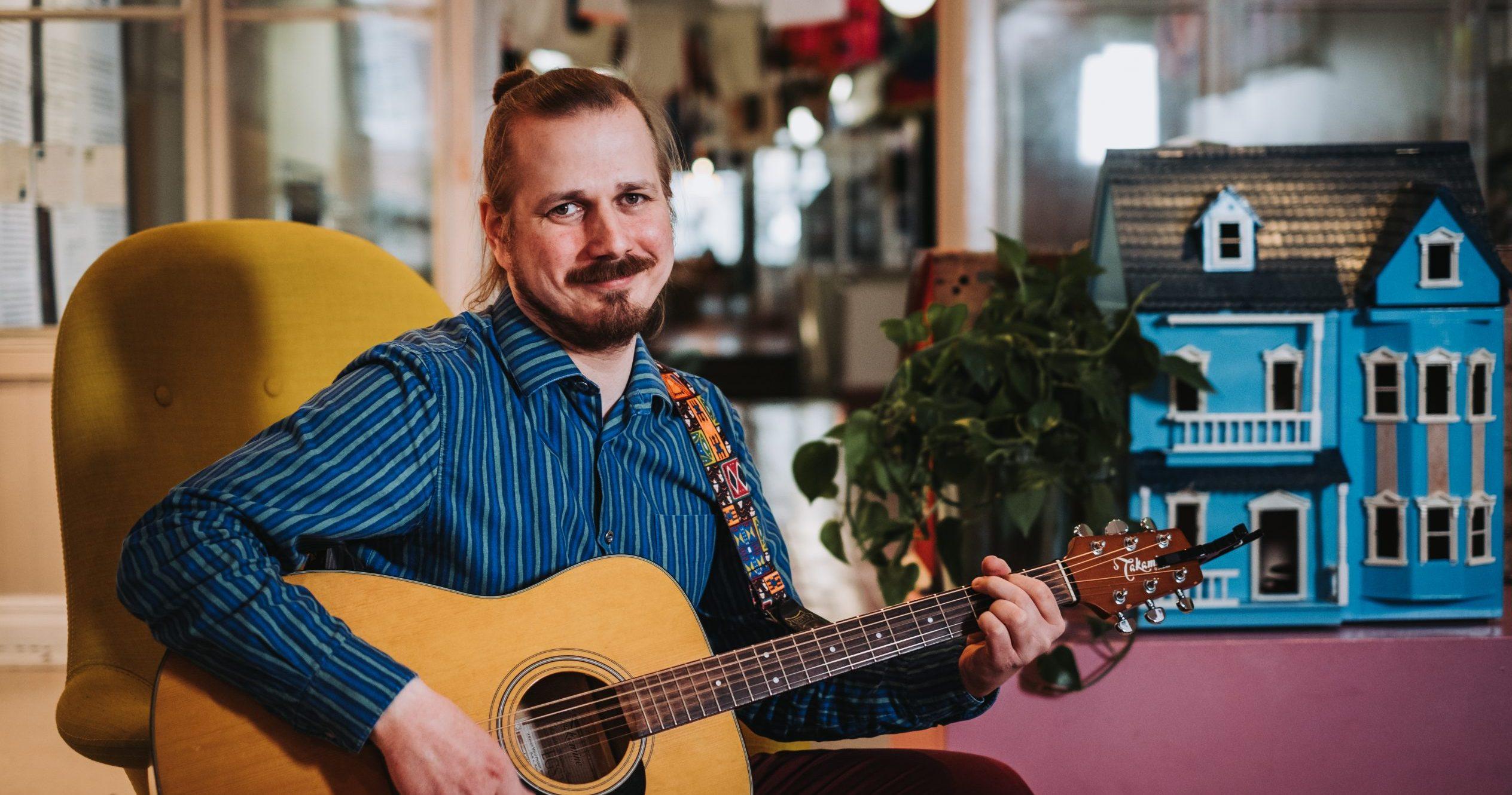 Ville Karttunen istuu kitara kädessään, taustalla sininen nukketalo.