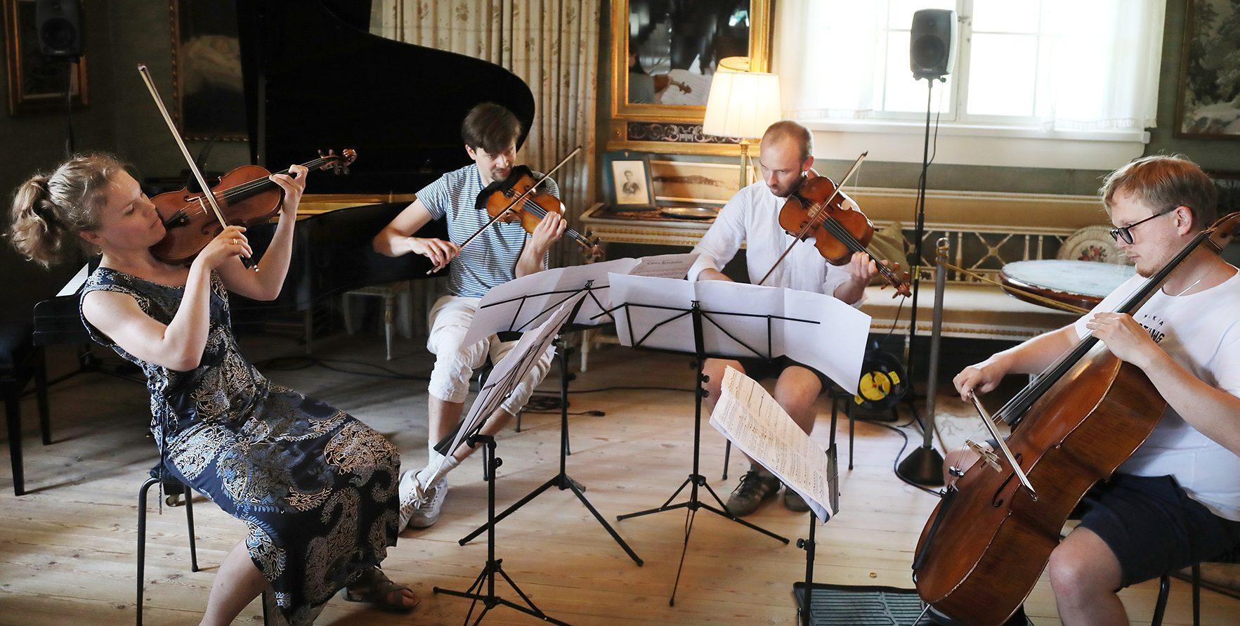 Kuvassa Kamus-kvartetti soittaa vanhassa salissa kolmea viulua ja selloa.