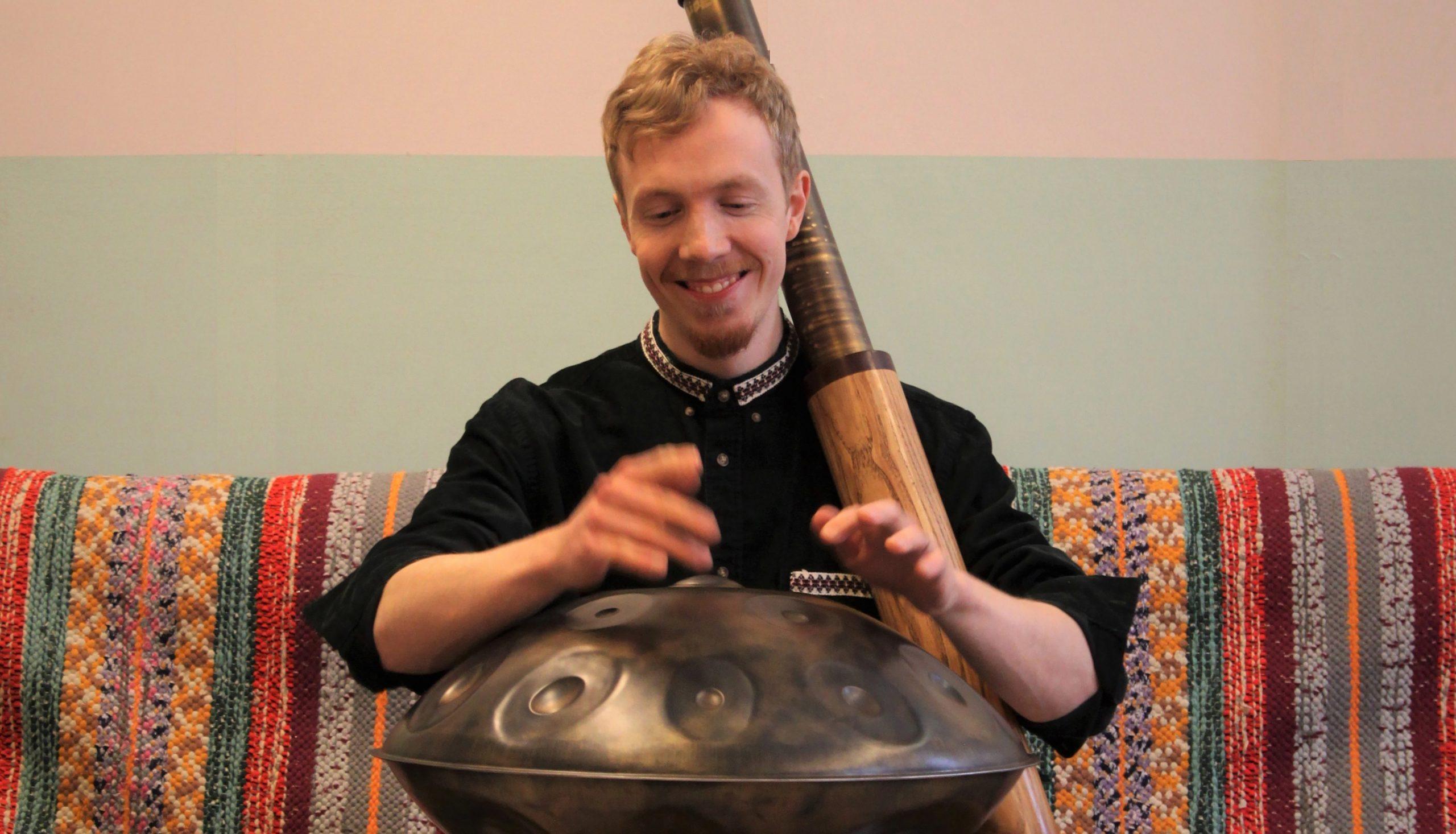 Kuvassa Julius Ranta soittaa hymyillen handpan-soitinta.