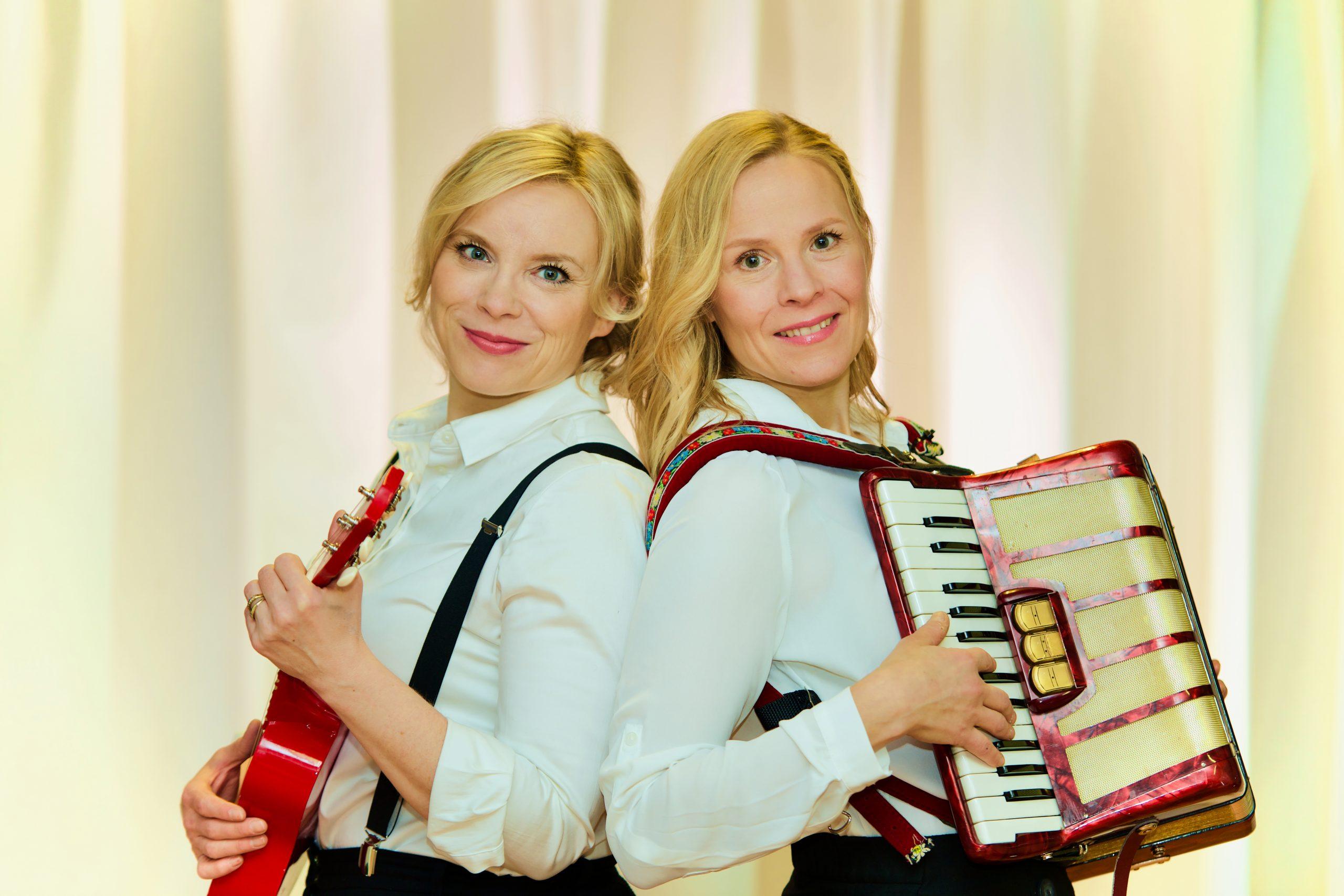 Kuvassa Susanna ja Maijan nojaavat selkä selkää vasten ukulele ja haitari käsissään.